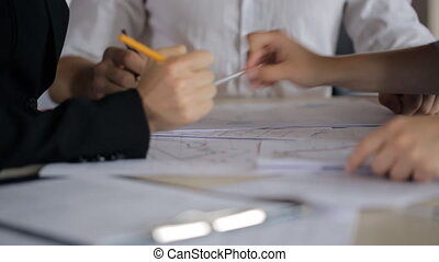It is close-up image of people discussing blueprints and...