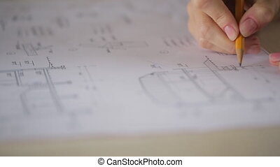 It is close up image of correcting blueprint or plan of...
