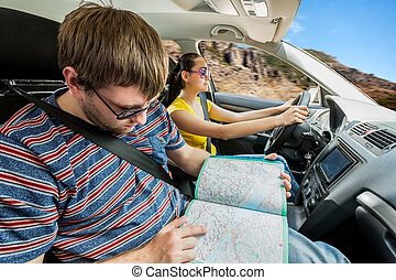 Couple travelling by car in the mountains, woman driving and...