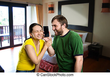Young couple having fun with a phone