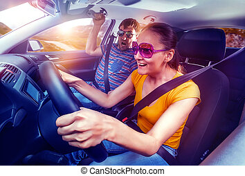Couple travelling by car, woman driving, man is scared