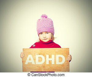 girl holding Board with inscription ADHD. - Little girl...