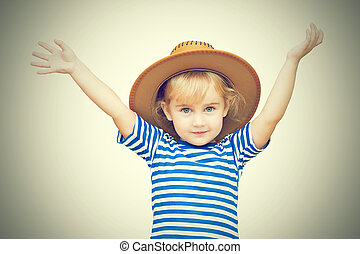 Sweet girl in a hat with raised arms