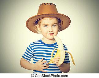 Little Funny girl eats banana - Little Funny girl in striped...
