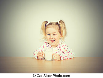Happy little girl with a glass of milk.