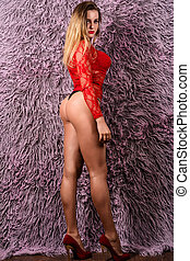 Attractive young blond girl in red lingerie on high heels