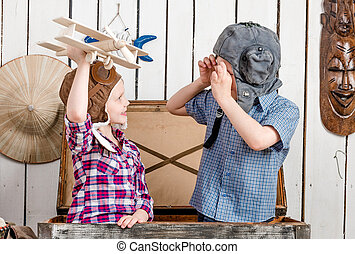 little girl with wooden plane in hand and boy in pilot hat