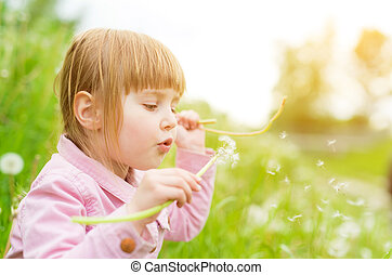cute little girl blowing off dandelions in park with green...