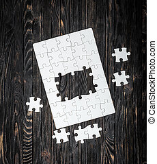 started puzzle with uncompleted center and pieces on dark...