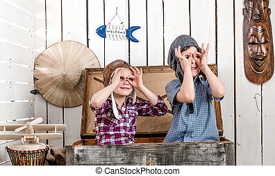 two little kids in pilot hats making glasses with hands -...
