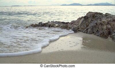 Foamy sea wave on sandy beach
