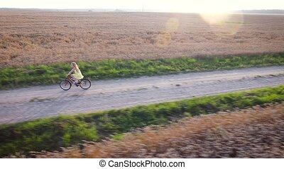 girl cycling Aerial view - girl cycling by road in the...