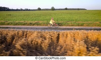 girl cycling. Aerial view - girl cycling by road in the...