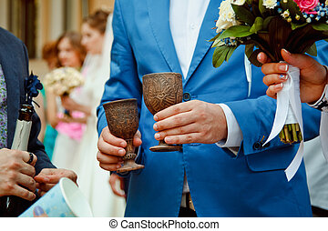 a pair of newlyweds holding vintage wooden glasses with...