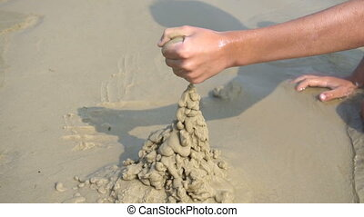 A boy builds a sandcastle - The boy builds a sand castle at...