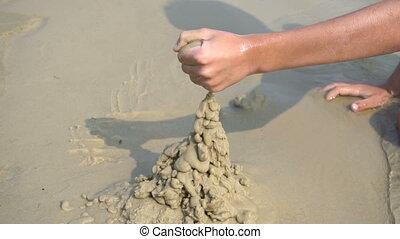 A boy builds a sandcastle - The boy builds a sand castle at...