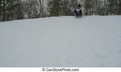 Young asian woman sliding down on snow slowmotion