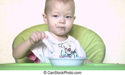 Baby girl eating porridge