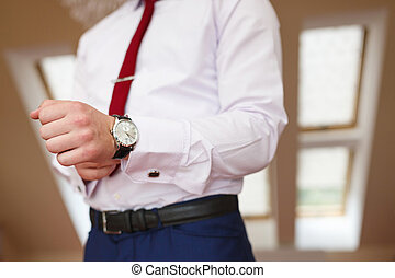 Man puts the watch - The groom puts his hand on the watch
