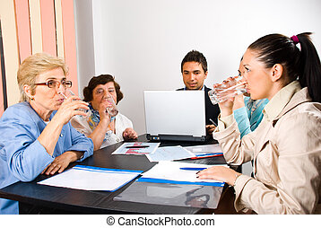 All business people drinking water at meeting and making a...