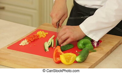 Chopping food ingredients - Chef is chopping vegetables on a...