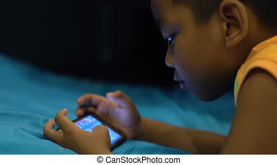 Little boy playing on smartphone.