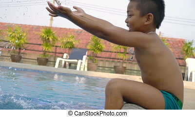 Little boy sits near swimming pool and plays with water...