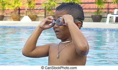 Little boy wearing goggles and diving in swimming pool...