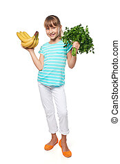 Smiling little girl holding fresh parsley and bananas -...