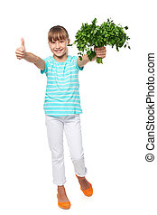 Smilinglittle girl showing fresh parsley and gesturing thumb...