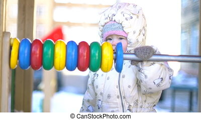 Baby girl playing with colorful abacus.