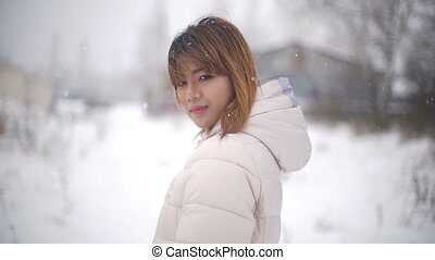 Young Asian Woman during snowfall. Slowmotion filmed at 120p