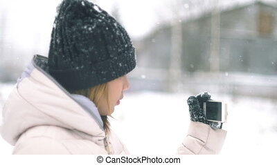 Young Woman taking photo winter landscape