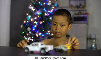 Little asian boy having fun with gift toy cars Christmas...