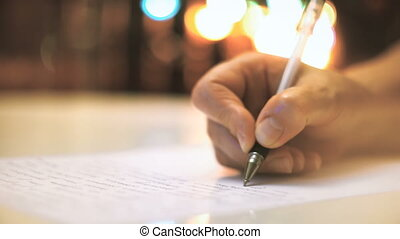 Hand is writing letter. Christmas lights on background -...