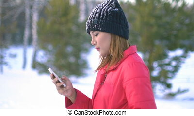 Young Woman using smartphone in winter park