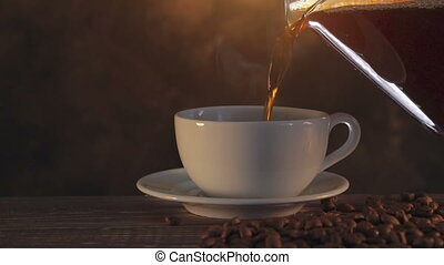 Fresh hot steaming aromatic coffee being poured into a white cup