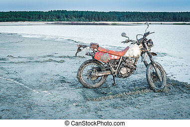 Dirty motorcycle in sand