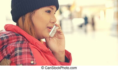 Happy asian Girl talking on cell phone in mall.