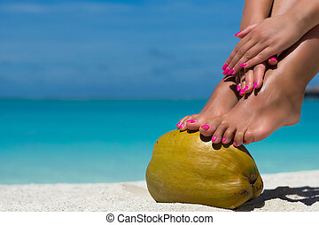 Female feet propped on coconut on the beach, blue sea...