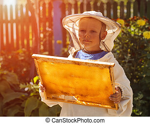 Young beekeeper boy holding frame of honeycomb