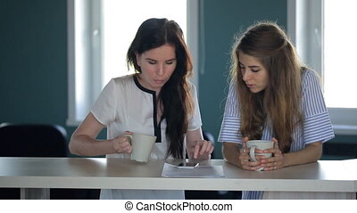Two women are looking in cellphone in time of coffee break....