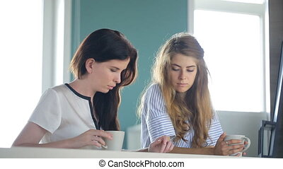 Two female are looking in cellphone in time of coffee break....