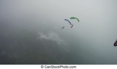 Parachutists flying in clouds. Extreme active sport. Adrenaline. Professional
