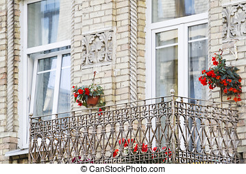 Old balcony of the brick house with flowers