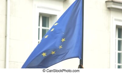 Wind blowing on EU flag. White building and blue banner....