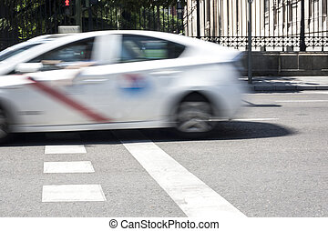 Taxicab crossing Madrid downtown street, Spain. Low motion...