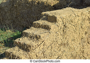 Old adobe wall closeup in sunny day. Sample construction of...