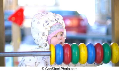 Baby girl playing with multicolor abacus in winter.