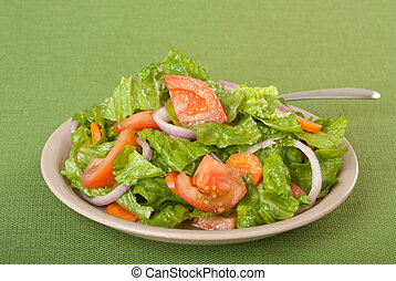 Tossed salad with lettuce, tomatoes, onions and carrots on a...